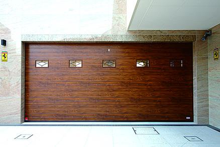 """ประตูโรงจอดรถ ซึ่งเป็นหน้าตาของโรงจอดรถ ใช้ประตูชัตเตอร์ EUGA ของ """"Sanwa Shutter"""" ประตูลายไม้ที่ดูขรึมเข้ากับผนังหิน ทำให้ดูเป็น""""ห้องงานอดิเรกของผู้ใหญ่"""" ส่วนประตู Maintenance Garage ซึ่งสูง ใช้ประตูชัตเตอร์แบบม้วนขึ้น"""