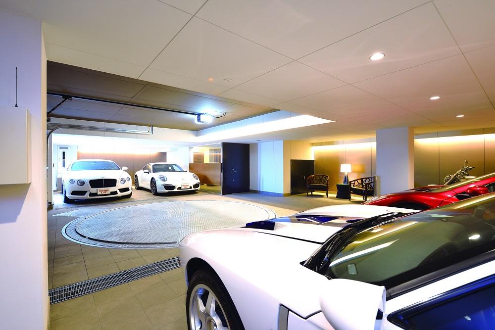 โรงจอดรถที่ซูเปอร์สปอร์ตคาร์จอดพัก มีพื้นที่กว้าง บรรยากาศงดงาม ตกแต่งด้วยของที่ใช้วัสดุต่างชนิดกันแต่คุมด้วยโทนสีเดียวกันคือขาวและน้ำตาล ทำให้ดูหมือนเลานจ์ในโรงแรมที่ดูสบาย ๆ ตามแบบที่คุณ T คิด